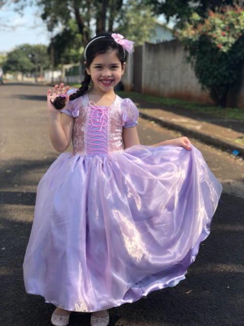 Menina segurando o vestido lilás e roxo.