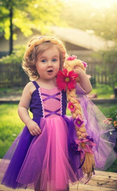 Criança pequenininha segura um aplique de trança enorme na mão. A sua saia é esvoaçante.