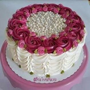 Bolo creme com flores magenta e rosa.