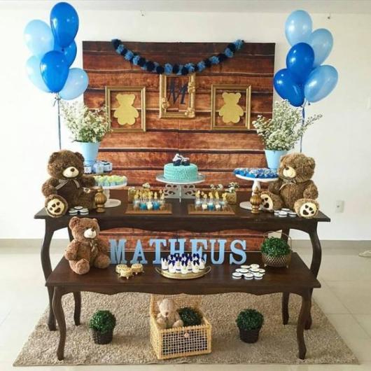 Decoração de ursinho com bexigas colocadas em cima da mesa.