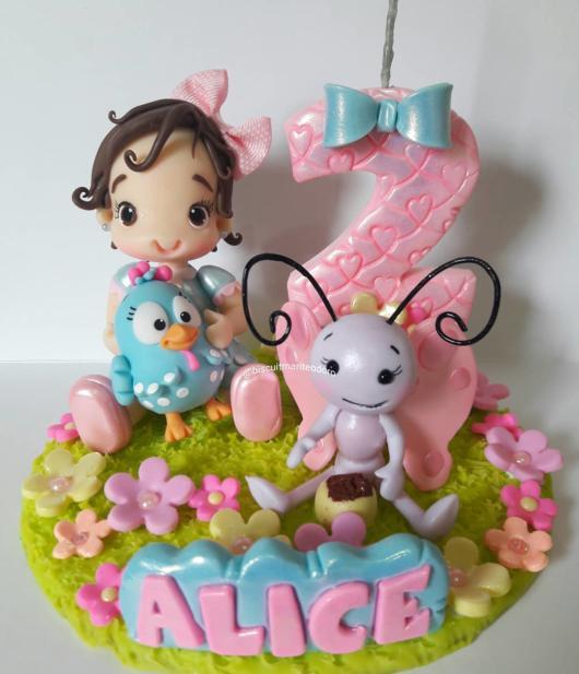 topo de bolo galinha pintadinha com uma menininha de boneca.