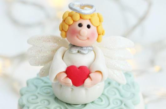 topo de bolo de batizado anjo segurando um coração