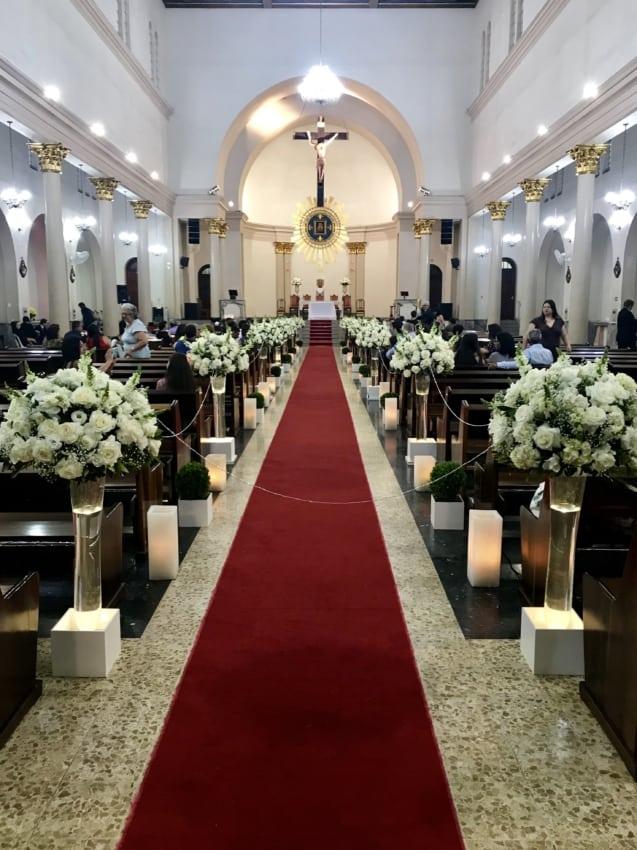 Igreja decorada com tapete vermelho e flores brancas