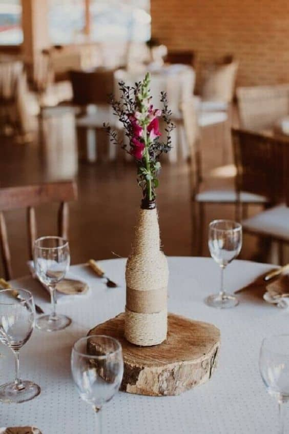arranjo de mesa com garrafa encapada de linha