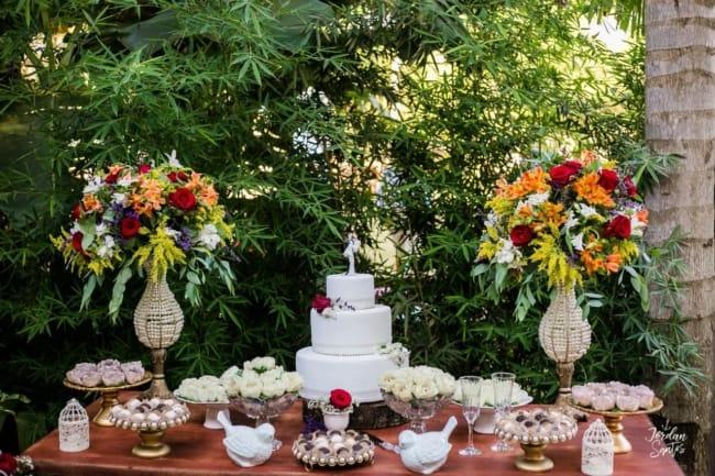 mesa de bolo de casamento simples com arranjos de flores