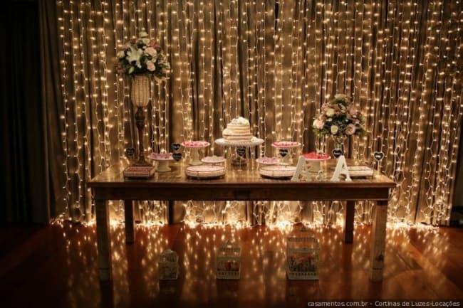 mesa do bolo com fundo de luzinhas