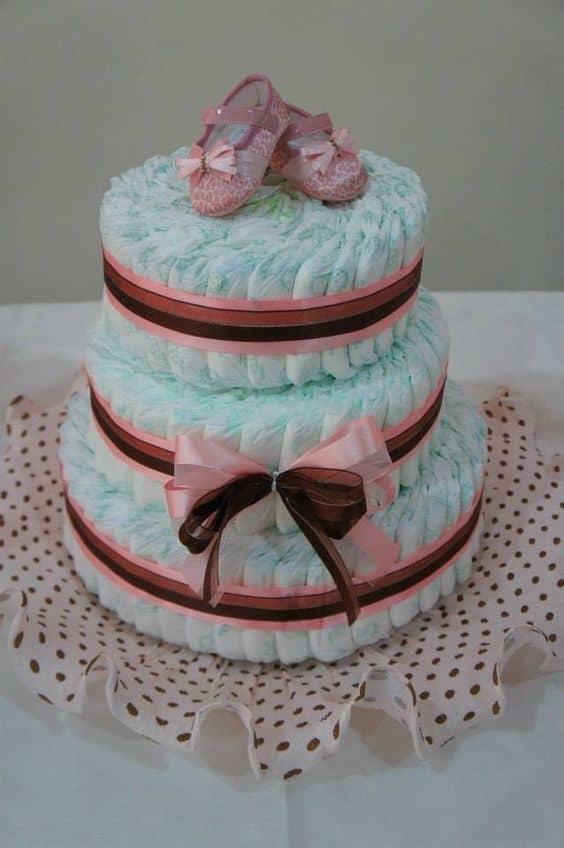 bolo de fraldas com sapatinhos decorando o topo
