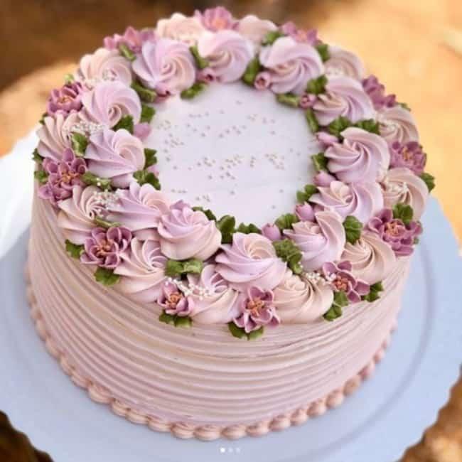 Bolo redondo rosa com flores de chantilly