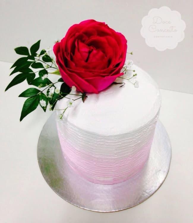 Bolo rosa e branco com flor grande no topo