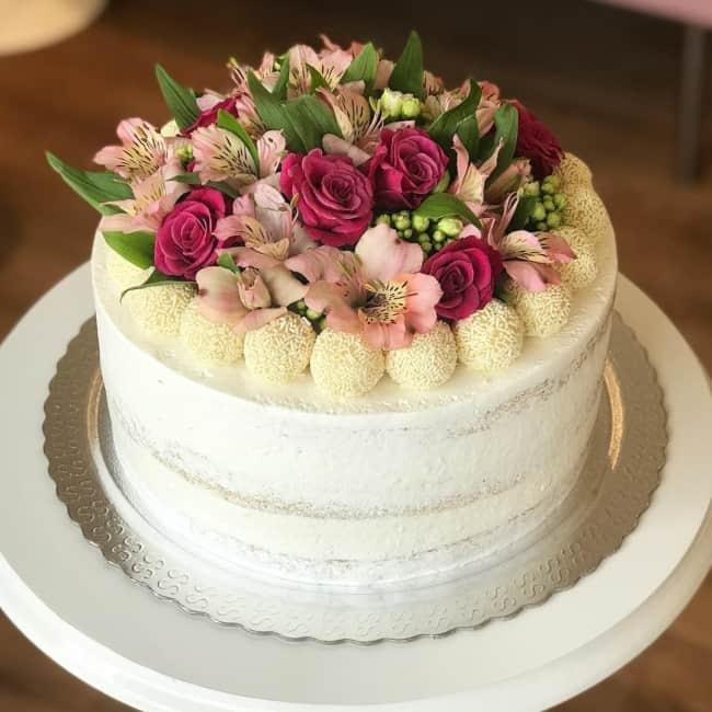 Decoração de bolo de noivado simples com doces e flores