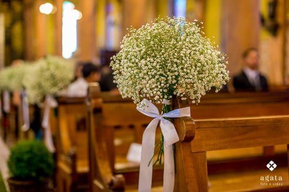 decoração de casamento na igreja com arranjos de flores nos bancos