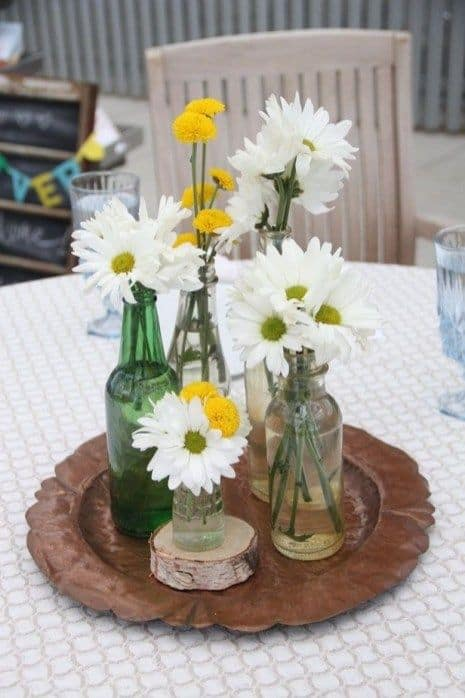 arranjo de mesa com garrafas e flores para casamento