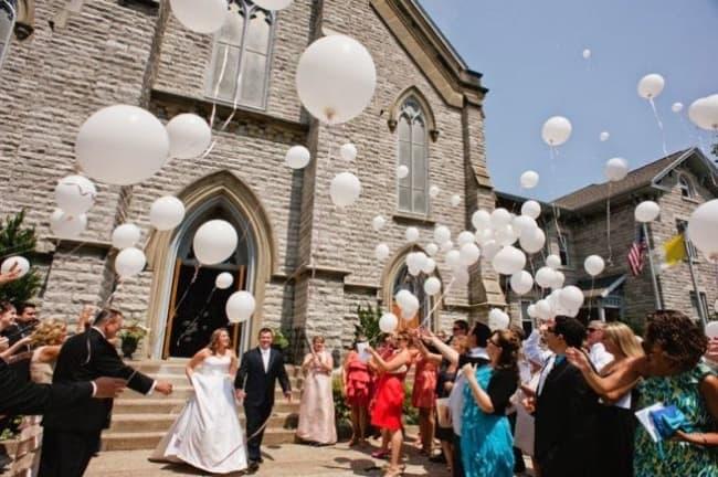 Saída dos noivos com balões brancos