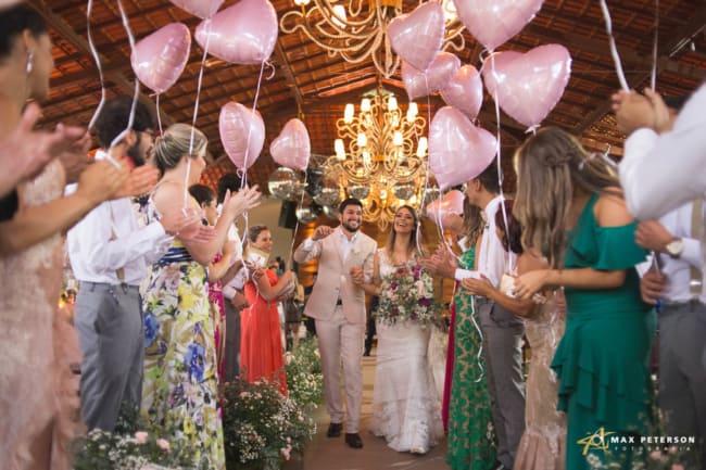 Saída dos noivos com balões rosa