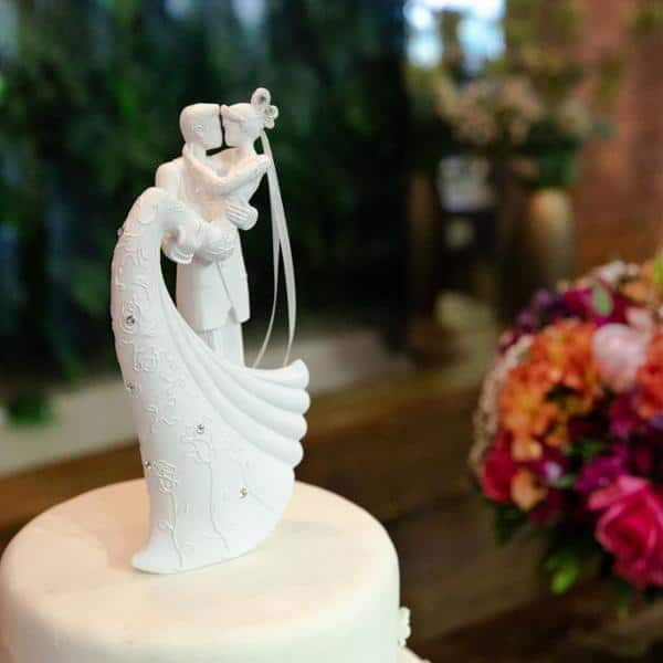 casal de noivinhos branco decorando bolo
