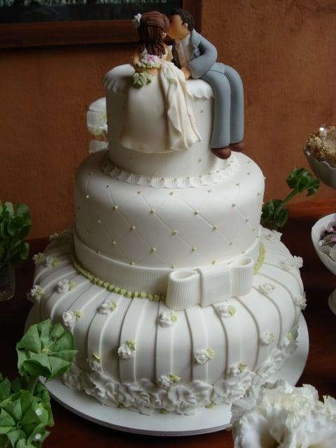 bolo de casamento com noivinhos de biscuit sentados