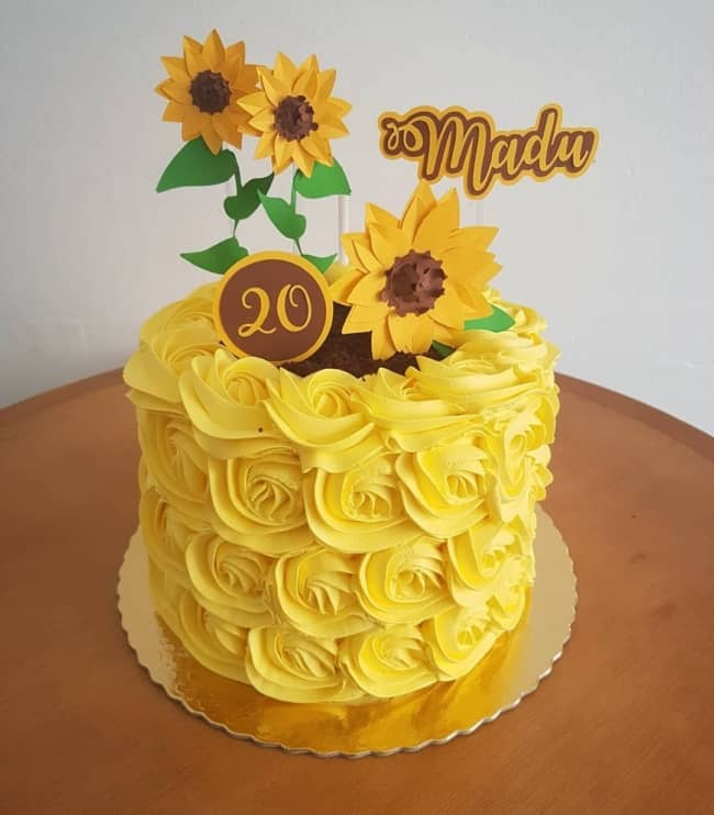 bolo de chantilly amarelo com girassois de papel no topo