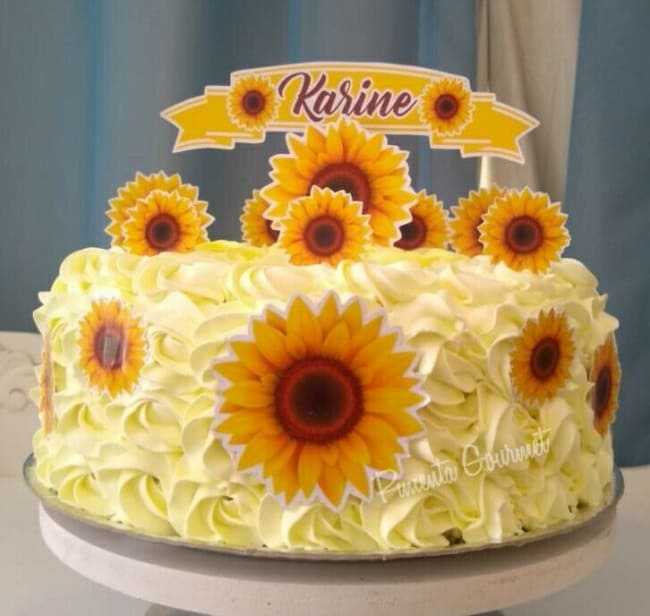 bolo redondo decorado com chantilly amarelo e toppers de girassol