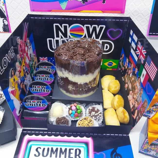 festa Now United na caixa com bolo e docinhos