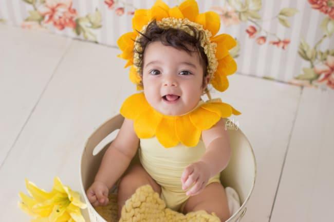 fantasia de bebe com acessorio de flor na cabeca