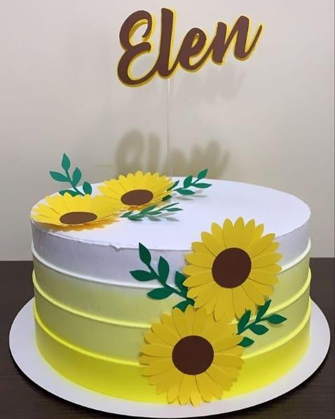 bolo redondo simples amarelo e branco decorado com toppers de girassol