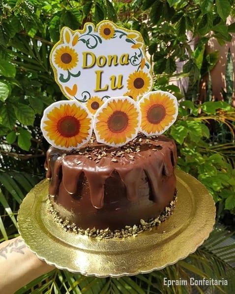 bolo redondo de chocolate decorado com toppers de girassol