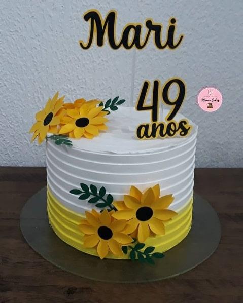 bolo de girassol redondado decorado em branco e amarelo