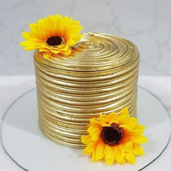 bolo redondo dourado com girassois dourados