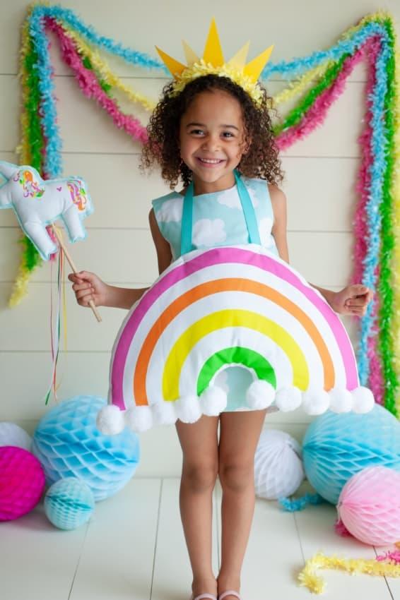 menina com fantasia de sol e arco iris