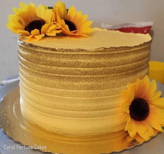 bolo amarelo e dourado com topo de flores artificiais