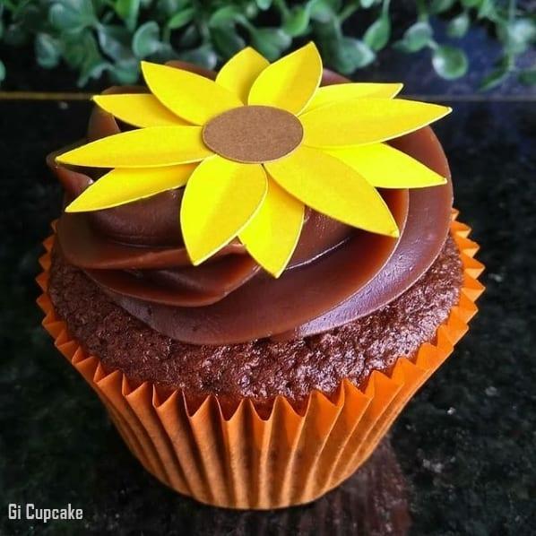 cupcake com cobertura de chocolate e girassol de papel