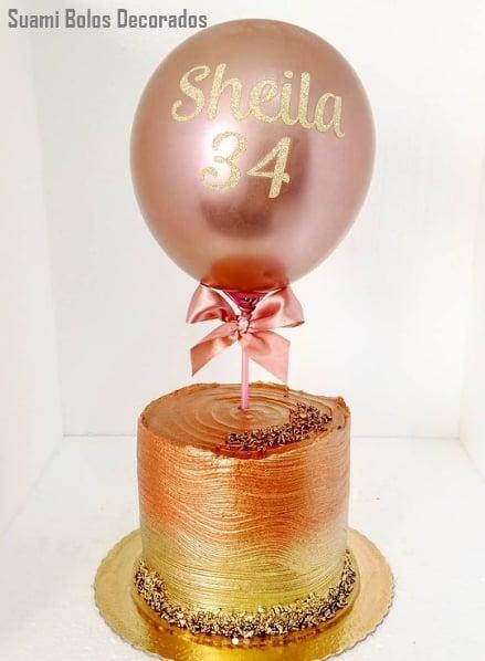 bolo rose gold e dourado decorado com balao personalizado