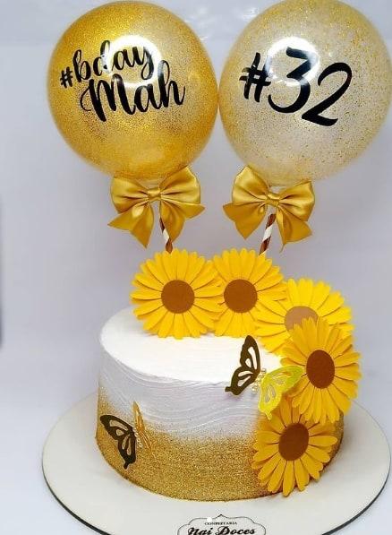 bolo com toppers de flores de girassol e baloes personalizados