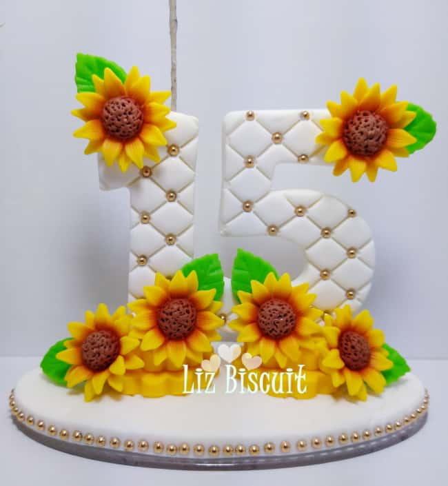topo de bolo de 15 anos com vela e girassois de biscuit