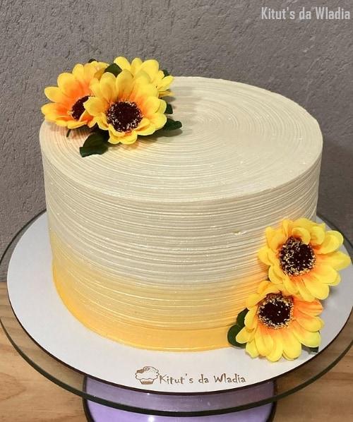 bolo com topo de flores artificiais de girassol