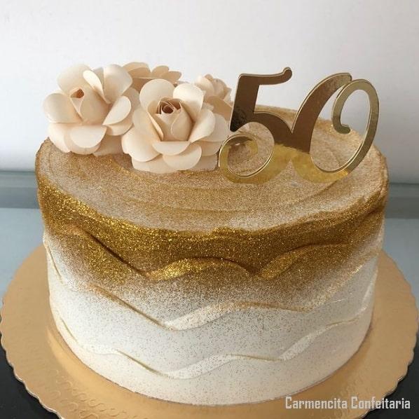 bolo de 50 anos dourado com flores de papel e topo dourado