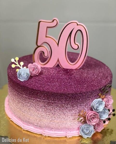 bolo rosa com glitter e topo de 50 anos