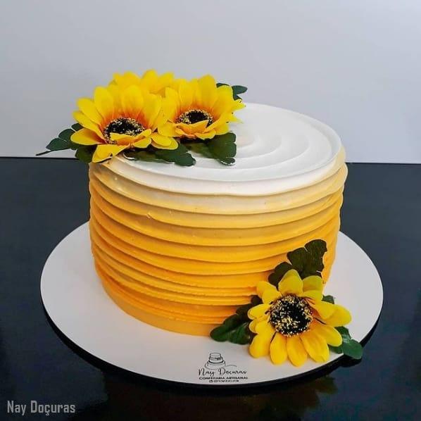 bolo degrade amarelo com flores artificiais de girassol
