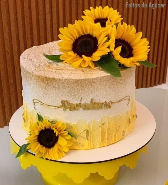 bolo redondo decorado com topo de flores de girassol