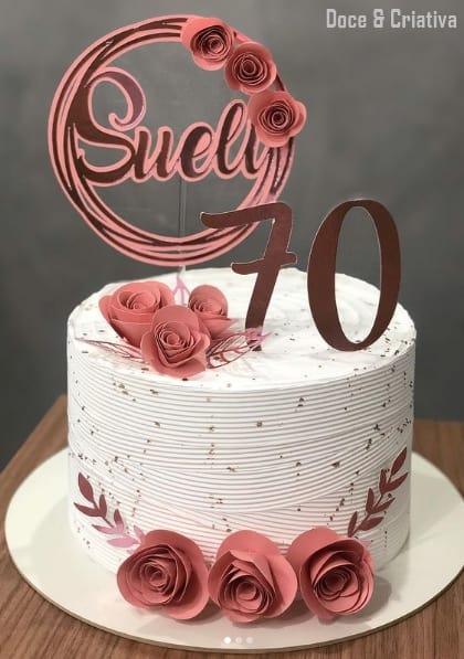 bolo branco com toppers rosa de 70 anos