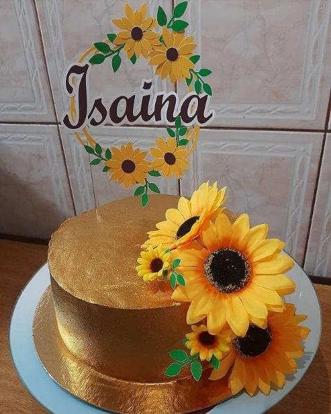 bolo dourado decorado com flores artificiais de girassol e topper