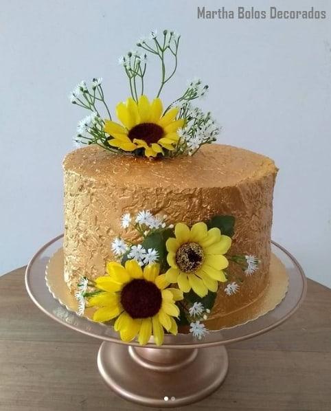 bolo dourado decorado com flores artificiais de girassol