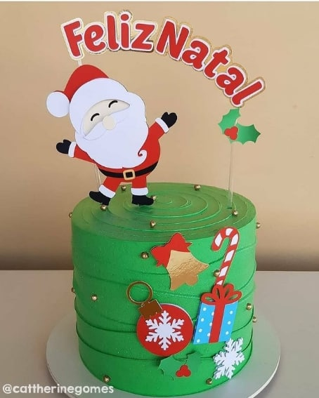 bolo decorado com topo de feliz natal e papai noel